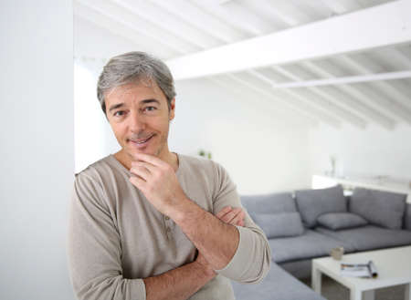 textspace: Mature handsome man standing in modern house Stock Photo