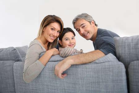 family sofa: Happy family of three relaxing in sofa