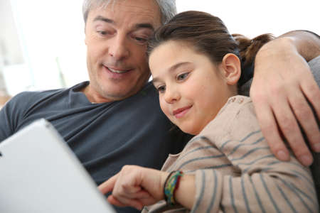 single father: Father and daughter playing with digital tablet Stock Photo