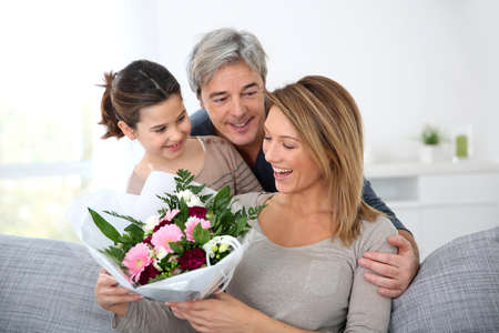 mom and dad: Family celebrating mothers day with bunch of flowers Stock Photo