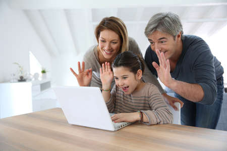 distant: Parents with kids making a distant call on internet Stock Photo