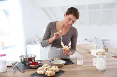 puffs: Woman in kitchen preparing cream puffs