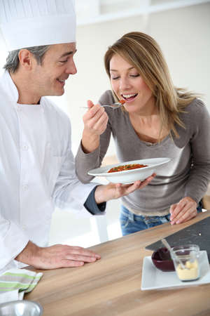 Chef preparing pasta dish for woman photo