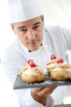 Chef holding plate of pastries towards camera photo