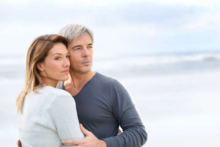 Cheerful middle-aged couple looking to the ocean photo