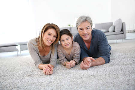 Middle-aged couple with little girl laying on carpet photo