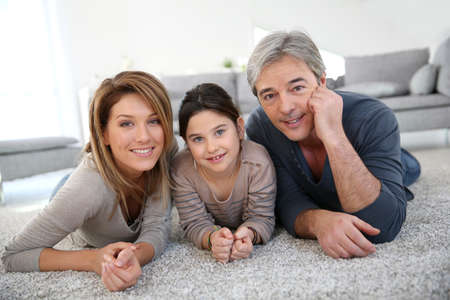 home interiors: Middle-aged couple with little girl laying on carpet Stock Photo