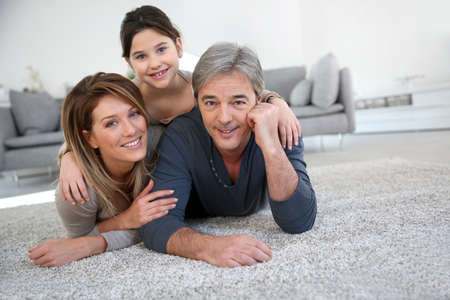 family house: Middle-aged couple with little girl laying on carpet Stock Photo