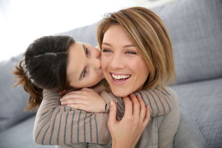 cheek to cheek: Little girl kissing her mom on cheek