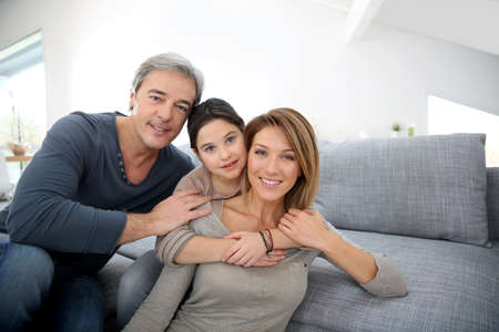 family couch: Parents with little girl relaxing on sofa