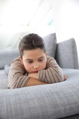 petite fille triste: Portrait de petite fille triste portant sur le canapé