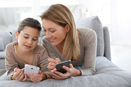 Mother and daughter playing games with smartphone photo