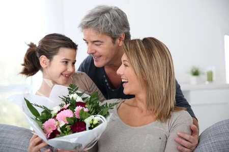 Family celebrating mother's day with bunch of flowers photo