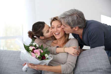 flores de cumpleaños: Familia que celebra el día de la madre con ramo de flores