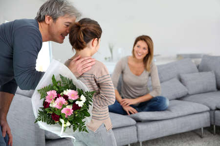 giving back: Young girl offering flowers to her mom