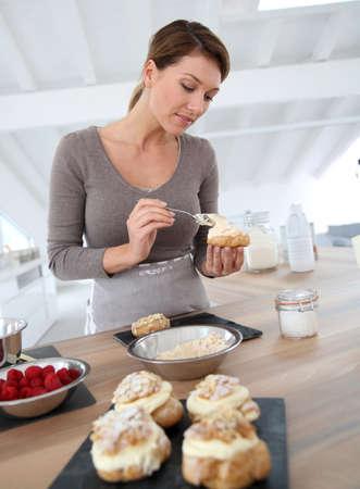 Woman in kitchen preparing cream puffs photo