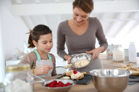 home baking: Mother and daughter preparing cream puffs Stock Photo