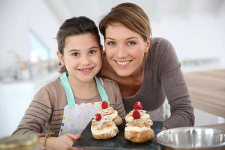 woman baking: Mother and daughter preparing cream puffs Stock Photo