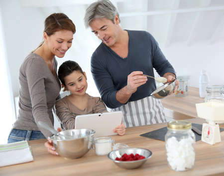Family in home kitchen preparing pastry photo
