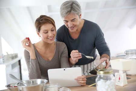 Couple in home kitchen cooking together and using tablet Stock Photo - 25841725