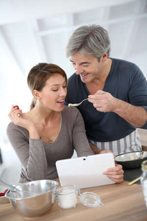Man having his wife tasting cake preparation photo
