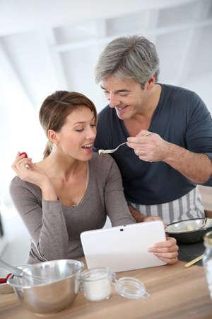 Man having his wife tasting cake preparation Stock Photo - 25841726