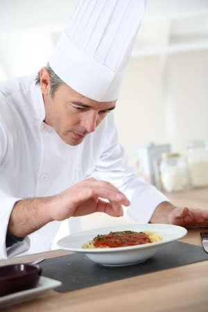 chef italiano: Cocinero en la cocina preparando el plato italiano
