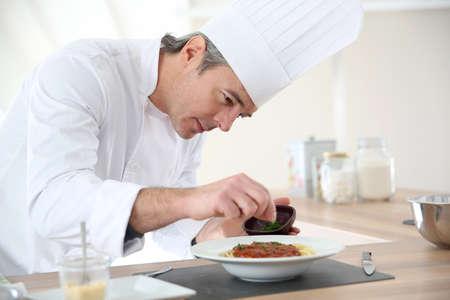 Cocinero en la cocina preparando el plato italiano