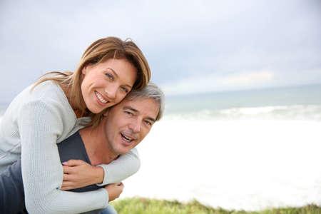 pareja de esposos: Apuesto hombre maduro que llevaba la mujer en la espalda Foto de archivo
