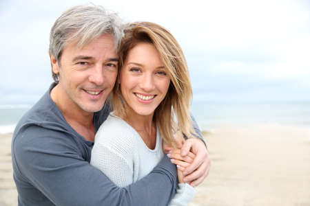 mature men: Cheerful mature couple embracing by the beach Stock Photo