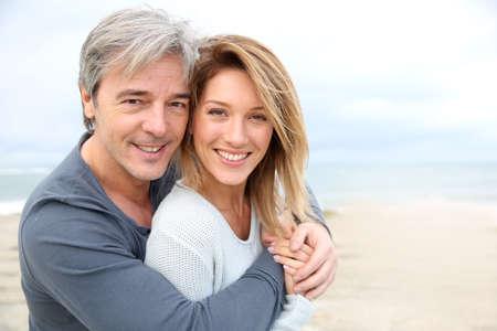 Vrolijke volwassen paar omarmen door het strand