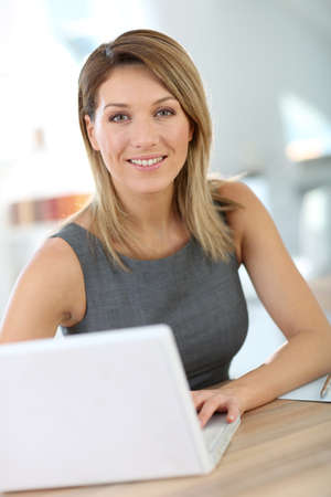 Portrait of businesswoman working on laptop photo