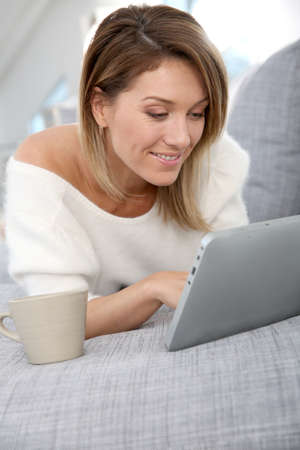 websurfing: Beautiful blond woman at home websurfing on internet