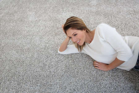 Upper view of woman relaxing on carpet at home Archivio Fotografico
