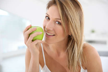 Beautiful woman giving bite to green apple  photo