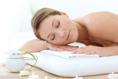 eyes shut: Attractive woman relaxing with eyes shut on massage bed