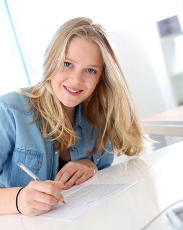 Smiling blond girl filling school application form Stock Photo