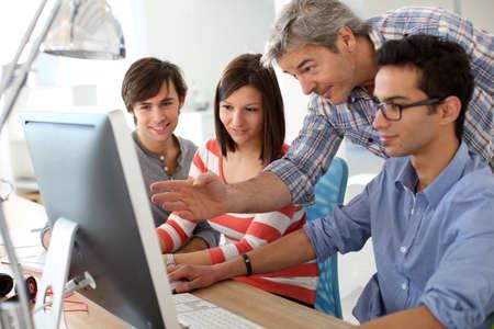 Leraar met studenten werken op desktop