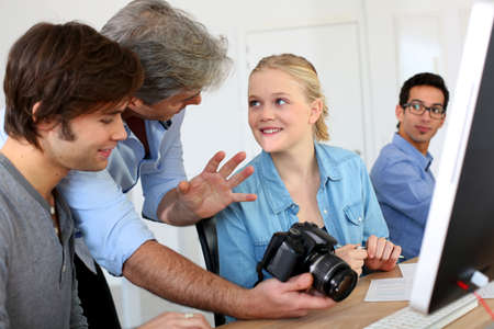 Teacher in class of photography with students photo