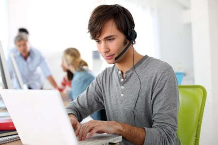 english language: Student with headset on doing English language test Stock Photo