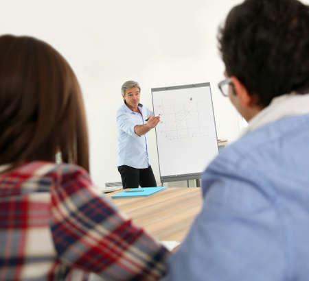 Teacher in business class doing marketing presentation photo