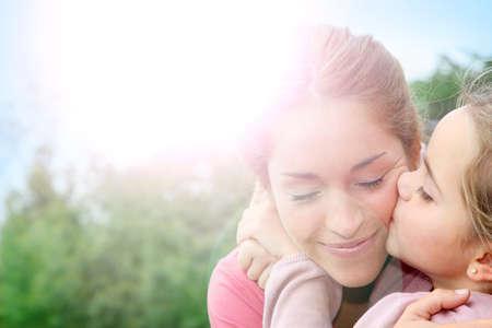 madre: Retrato de niña da un beso a su mamá
