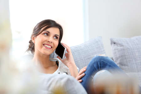 women talking: Young cheerful woman in couch talking on mobile phone Stock Photo