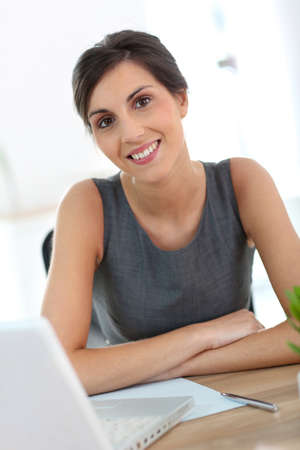 Beautiful businesswoman in office working on laptop photo