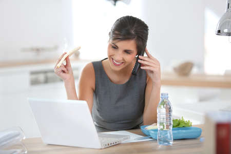 Busy businesswoman having lunch in office photo