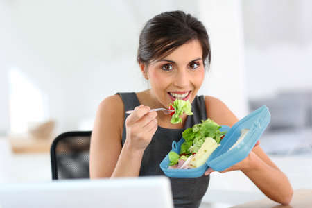 having lunch: Busy businesswoman having lunch in office