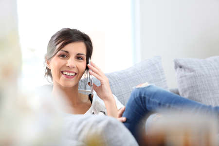 Young cheerful woman in couch talking on mobile phone photo