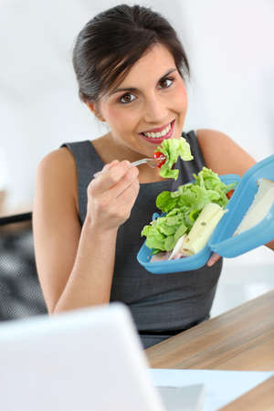 Businesswoman eating from lunch box in office