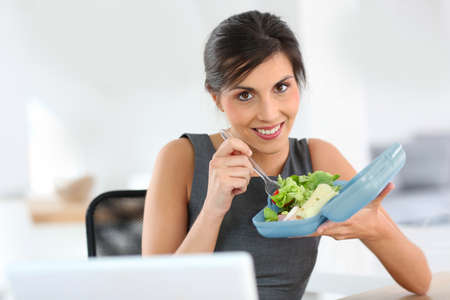 Businesswoman eating from lunch box in office photo