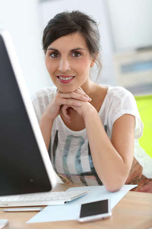 young woman at work in front of desktop photo